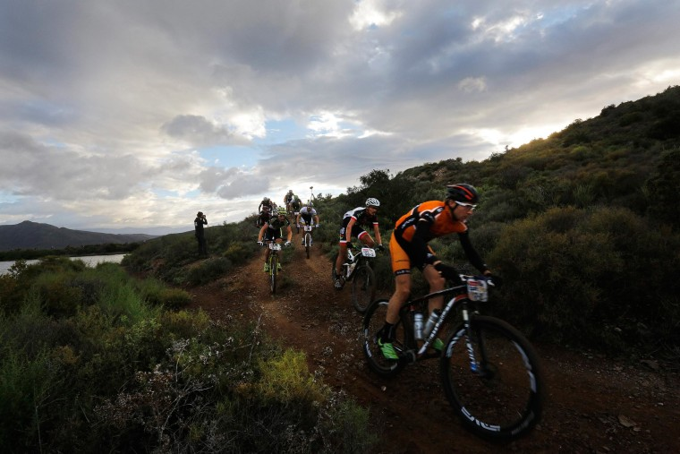 Image: Mountain bikers ride through a drop-off during the longest stage of the annual ABSA Cape Epic mountain bike stage race near Cape Town, South Africa