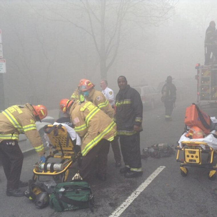 Image: Firefighters attend to an injured firefighter at the scene of a nine-alarm fire in Boston, March 26.