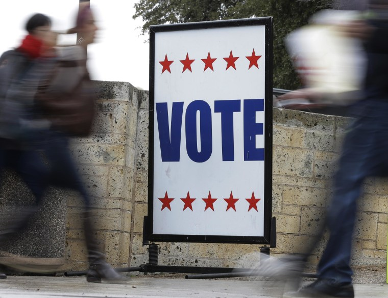 Image: Pedestrians pass voting signs near a voting sign.
