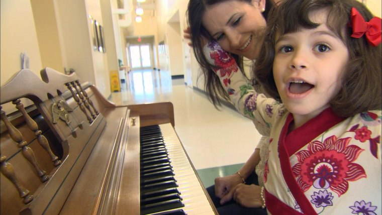 Kim Cristo sits at a piano with her daughter Ava Cristo, age 6, who has autism. New research suggests gut bacteria may play a role in some of the symptoms of the disorder.