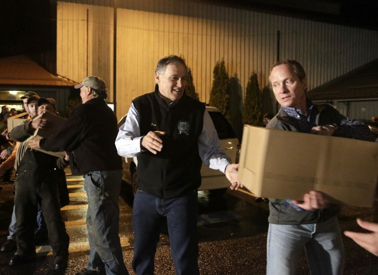 Washington Gov. Jay Inslee helps community members unload a truckload of donated goods at the Community Center in Darrington, Wash.