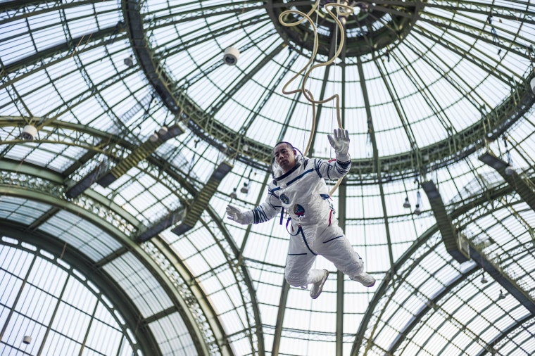 Image: Chinese artist Li Wei performs dressed as an astronaut at the Grand Palais, in Paris, France