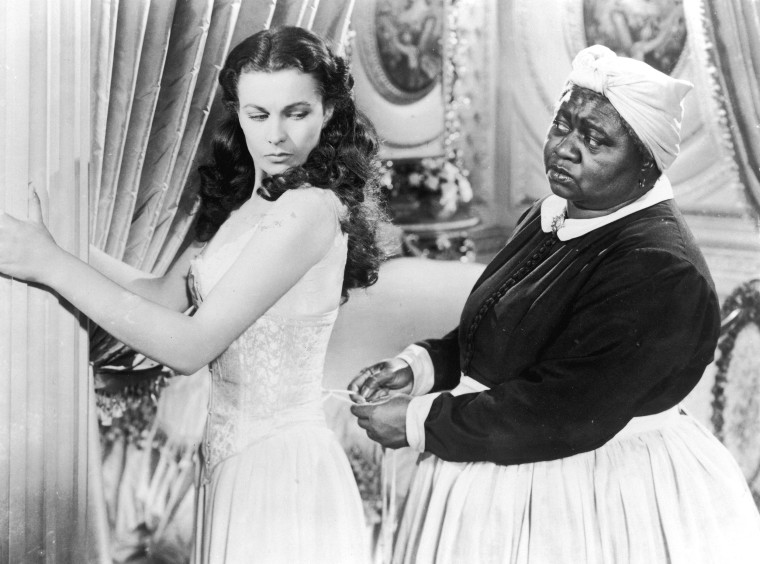 British actor Vivien Leigh holds on to a pillar as American actor Hattie McDaniel tightens her corset in a still from the film, 'Gone with the Wind,' directed by Victor Fleming.