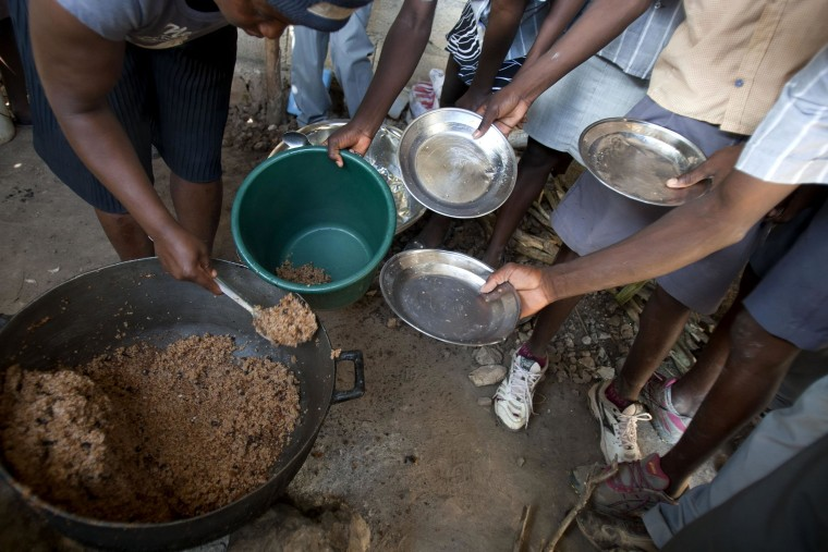 Image: Students hold out their plates as the school cook ladles out a bulgur wheat and bean dish at a public school in Bombardopolis, Haiti.