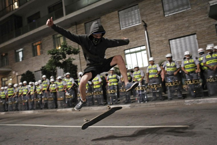 A demonstrator performs a trick with his skateboard in front of military police during a protest against the 2014 World Cup in Sao Paulo on Friday. Protesters are angry that billions of dollars worth of public funds have been spent on 12 stadiums for the cup, which kicks off in São Paulo June 12.