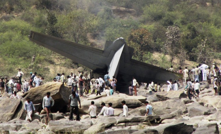 Image: Onlookers stand next to the debris of a crashed Indian Air Force C-130J Hercules aircraft  in Madhya Pradesh