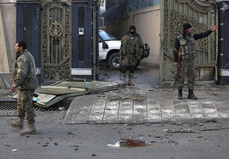 Image: Afghan security personnel stand guard outside a guesthouse, the site of a suicide attack, in Kabul