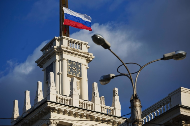 Image: The national flag of Russia flies atop a city clock tower in Sevastopol, Crimea