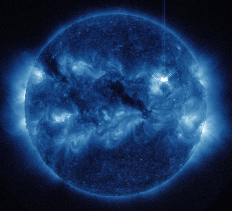 An extreme ultraviolet image from NASA's Solar Dynamics Observatory shows a flare erupting from the sun's disk, just above and to the right of center, at 1746 GMT (1:46 p.m. ET) Saturday.