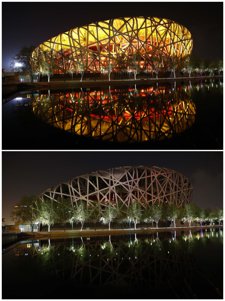 Image: The National Stadium, also known as 'Bird's Nest', reflected in a lake before and during Earth Hour at Olympic Park in Beijing,