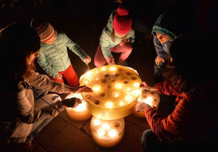 Image: People light candles to celebrate Earth Hour in a park in Bucharest