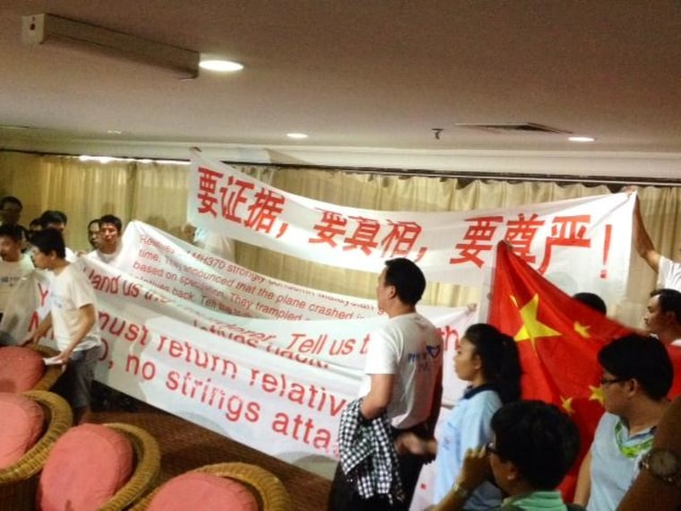 Image: Chinese relatives of passengers on missing Malaysia Airlines Flight 370 display banners and chant