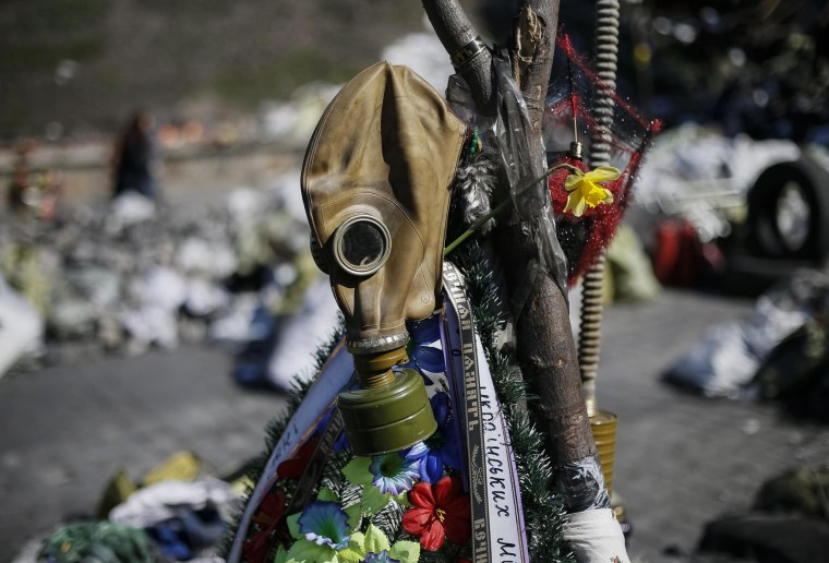 Image: A gas mask and flowers are seen at the site of the recent clashes in Kiev