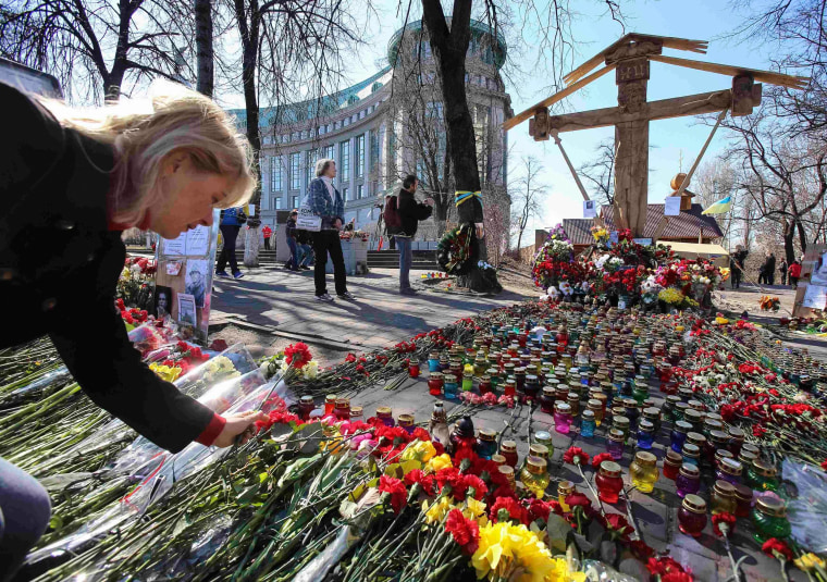 Image: A woman lays flowers at the site of the recent clashes in Kiev