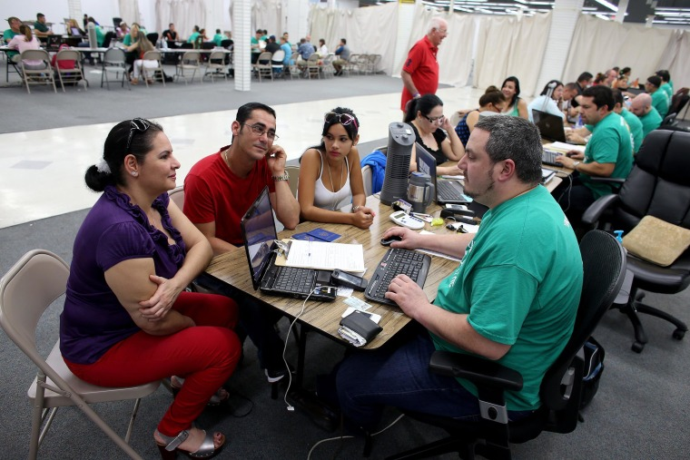 Image: People purchase health insurance from an agent from Sunshine Life and Health Advisors in Miami.