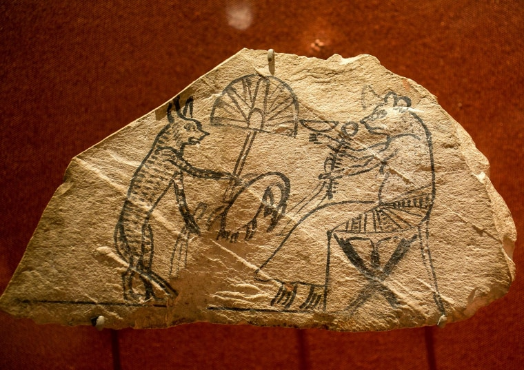 Image: A limestone with pigment shows a scene of a cat and mouse, in which animals perform human tasks
