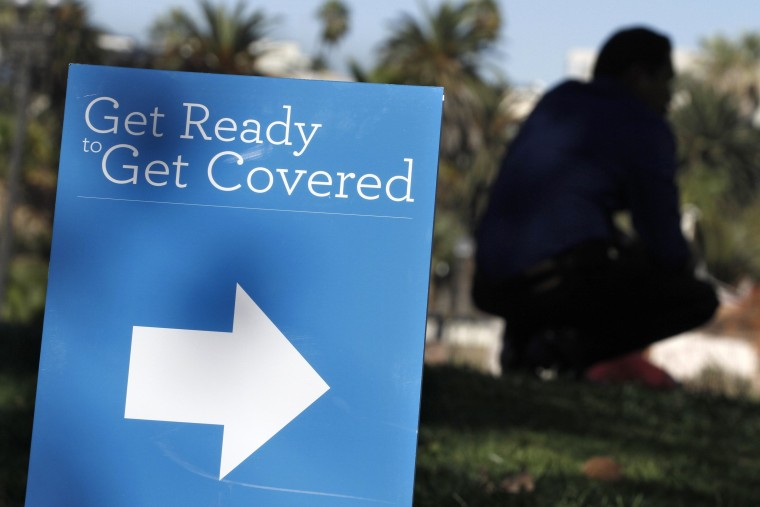 Image: A man is silhouetted behind a sign at an Affordable Care Act outreach event hosted by Planned Parenthood for the Latino community in Los Angeles, California
