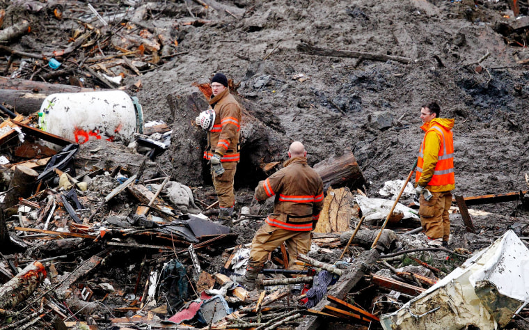 Image: Searchers stand for a moment of silence at the scene of a deadly mudslide in Oso, Wash.
