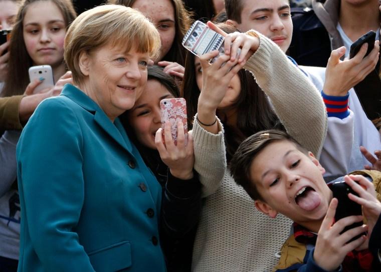 Image: Students take mobile phone 'selfies' with German Chancellor Angela Merkel as she arrives for visit at Robert-Jungk Europe high school in Berlin