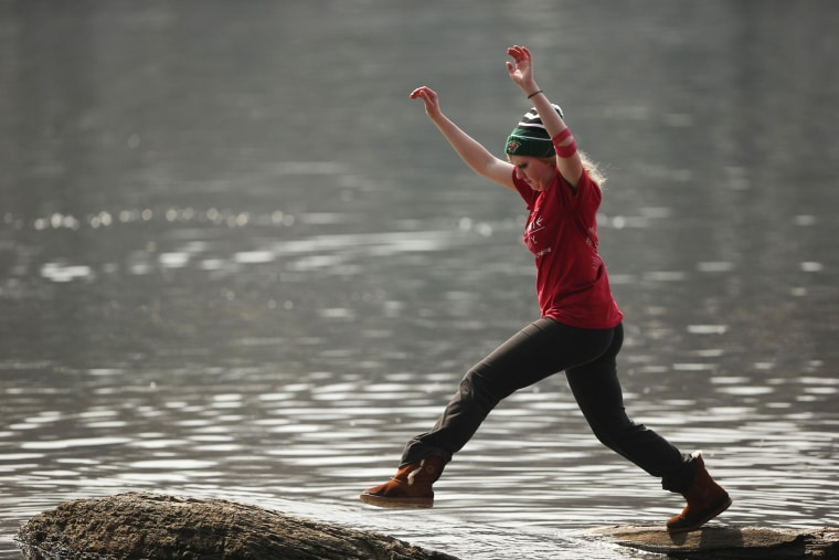 Kayla Chase leapt from one stone to another further out in the water along the banks of the Mississippi River in Minneapolis on Sunday, March 30, 2014. (AP Photo/The Star Tribune, Jeff Wheeler)