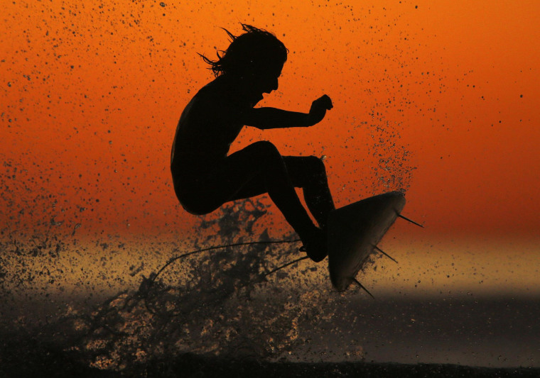 Image: Surfer Cole Clisby rides his surfboard off the top of a wave after sunset in Leucadia