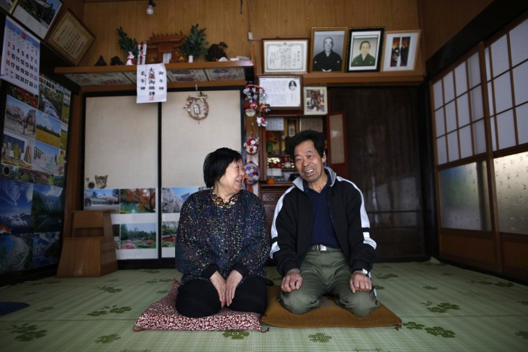Image: A man and his wife, who evacuated from the Miyakoji area of Tamura three years ago, smile after they returned to their home in Tamura, Fukushima prefecture