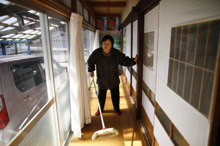 Image: A woman, who evacuated from the Miyakoji area of Tamura three years ago, dusts off her house after she returned to her home in Tamura, Fukushima prefecture