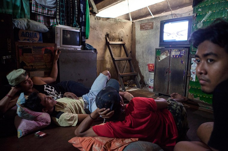 Image: A platform under the Kuningan bridge, dwellers watch TV and play games in what they call the living room.