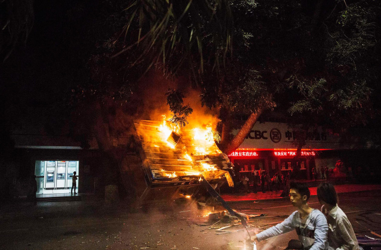 Residents ride past a burning public security kiosk during a protest against a chemical plant project, on a street in Maoming, Guangdong province, China, early on April 1, 2014.