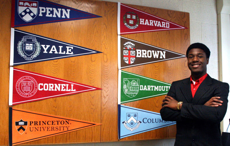 Kwasi Enin poses with banners from the Ivy League colleges where he was accepted.