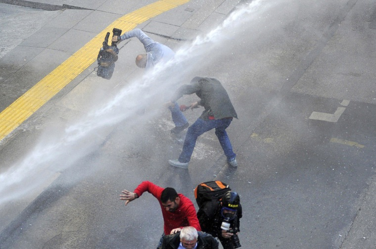 Image: Media members run as riot police use water cannons to disperse protesters outside the Supreme Electoral Council (YSK) in Ankara