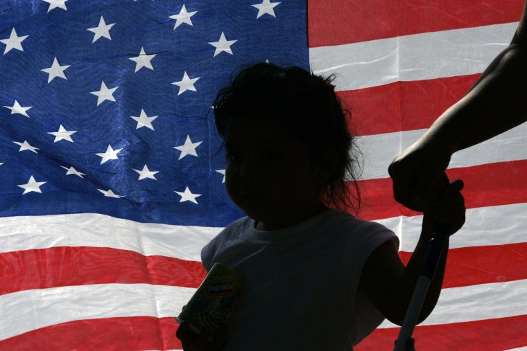 Image: A child is silhouetted against an U.S. flag