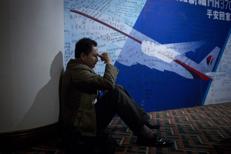 A man, one of the relatives of Chinese passengers on-board Malaysia Airlines Flight 370, rests near a board covered with written wishes at a hotel in Beijing, China, on March 29.