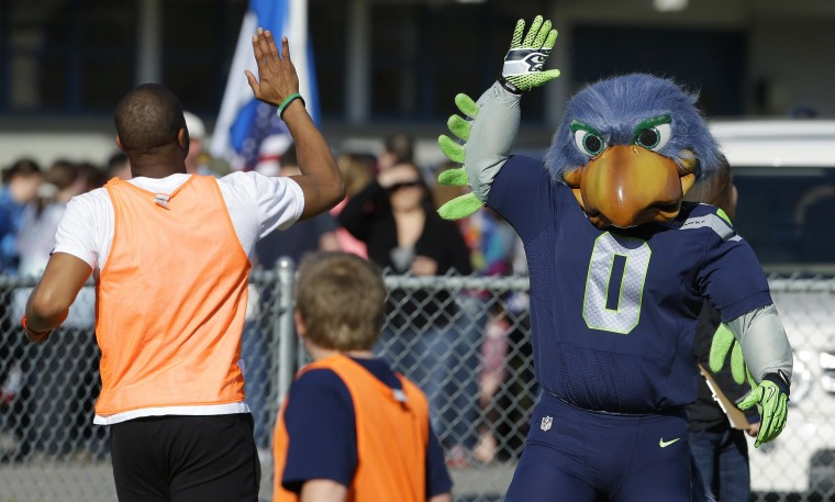 Image: Blitz, the Seattle Seahawks NFL football mascot, gives a high five at a community gathering in Darrington, Wash.