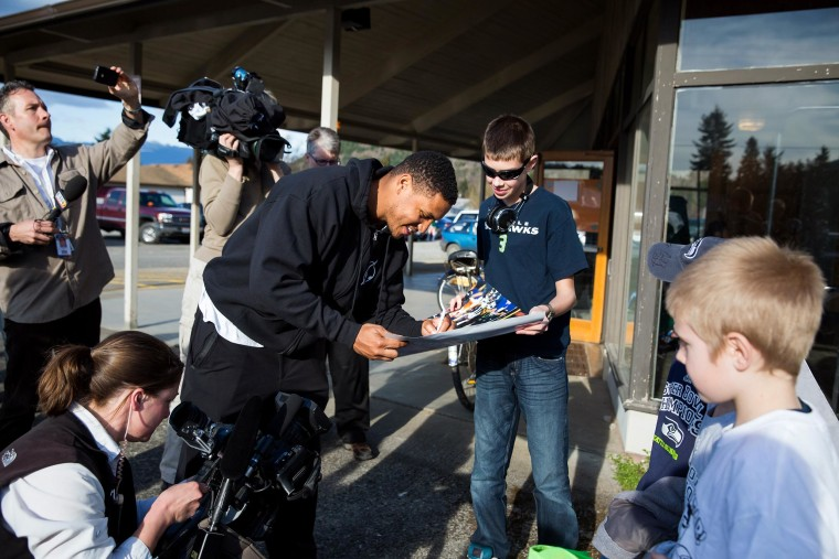 Image: Seattle Seahawks linebacker Malcolm Smith, center, signs autographs outside the Darrington Community Center