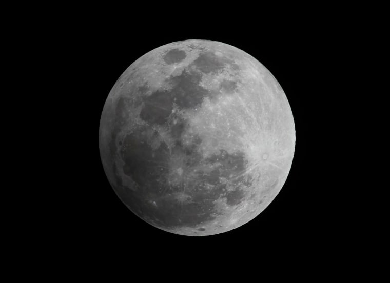 Image: A penumbral eclipse of the moon in the night sky in Manila