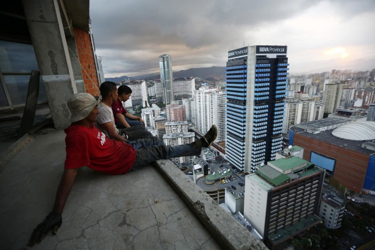 """Image: Men rest after salvaging metal on the 30th floor of the """"Tower of David"""" skyscraper in Caracas"""