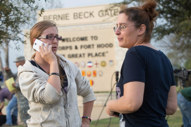Krystina Cassidy and Dianna Simpson attempt to make contact with their husbands who are stationed inside Fort Hood, while standing outside of the Bernie Beck Gate, on April 2, 2014, in Fort Hood, Texas.