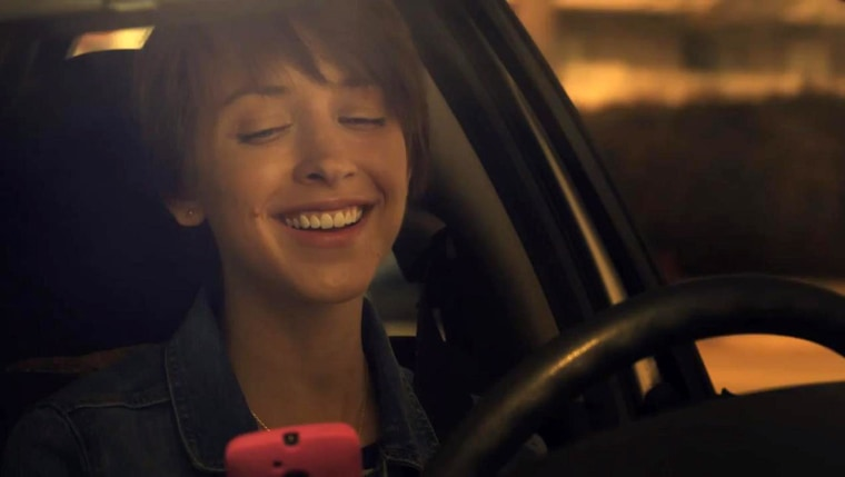 Image: A young woman looks at her cellphone while driving as part of an advertisement from Distraction.gov