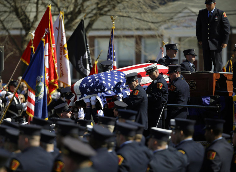Image: The casket containing the body of firefighter Michael R. Kennedy is lowered from Engine 33 before his funeral outside Holy Name Church in Boston