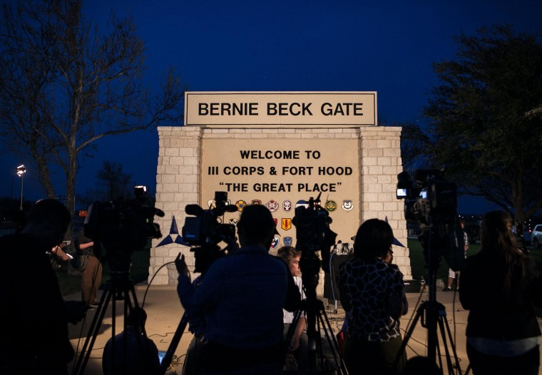 Image: The media and Public Affairs military personnel wait for a press conference to be held outside the Bernie Beck Gate
