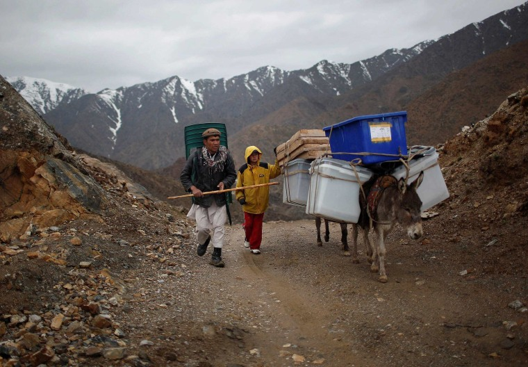 Image: Afghan man and boy lead donkeys loaded with ballot boxes and other election material to be transported in polling stations which are not accessible by road in Shutul