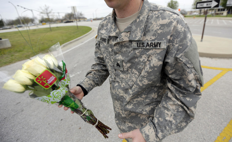 An unidentified soldier holds flowers dropped off at Fort Hood's main gate for shooting victims, Thursday, April 3, 2014, in Fort Hood, Texas. A soldier opened fire Wednesday on fellow service members at the Fort Hood military base, killing three people and wounding 16 before committing suicide. (AP Photo/Eric Gay)