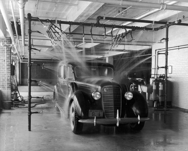 Image: An automobile sits under pipes with multiple nozzles spraying water at a car wash