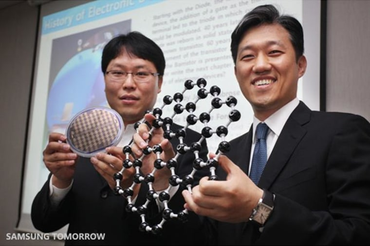 Samsung researchers hold up models of graphene and transistors made of the material at a 2012 event.