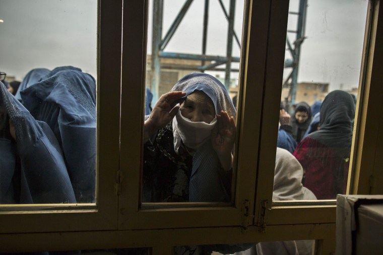 Image: An Afghan woman looks through a window as she waits for her turn to vote at a polling station in Mazar-i-sharif
