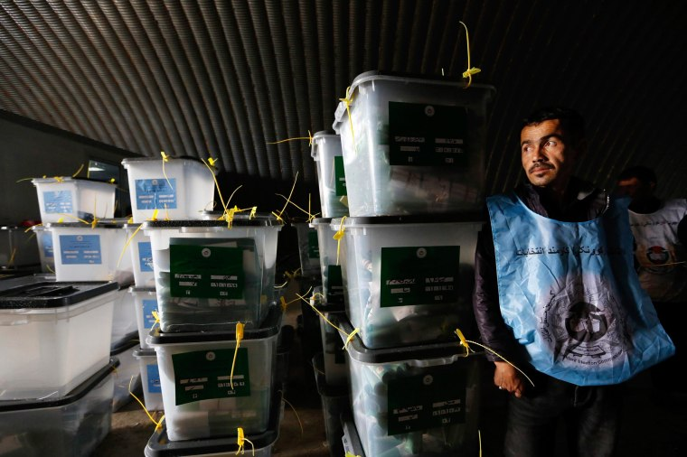 Image: Afghan election worker stands next to ballot boxes at a counting centre in Kabul