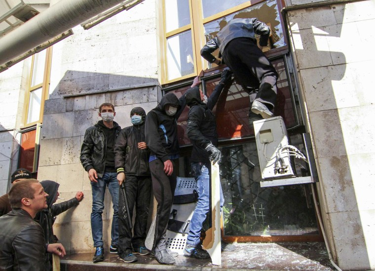 Image: Pro-Russia protesters attempt to enter through a broken window as they storm the regional government building in Donetsk