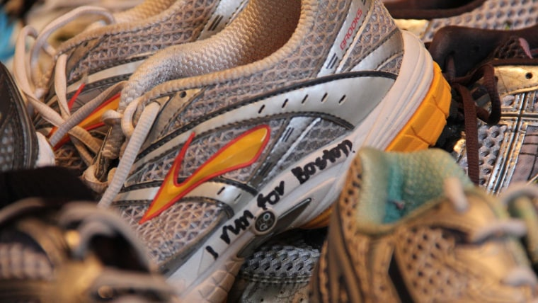 """Hundreds of runners tied their sneakers to the police barricades in Copley Square that became a memorial to the Boston Marathon bombings. Curator Rainey Tisdale was part of a team that carefully untied those running shoes, cleaned, and collected them for the """"Dear Boston"""" exhibit."""