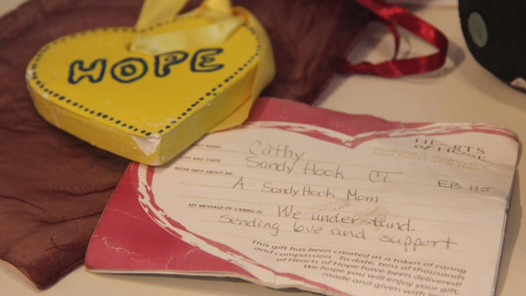 """People from around the world left messages of hope and support on the makeshift memorial in Copley Square in the weeks following the Boston Marathon bombings. One message came from a Sandy Hook mother who wrote, """"We understand. Sending love and support."""""""